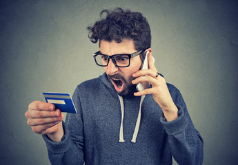 Screaming angry man solving problems with credit card