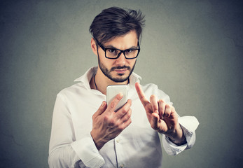 Man with smartphone showing rejecting sign