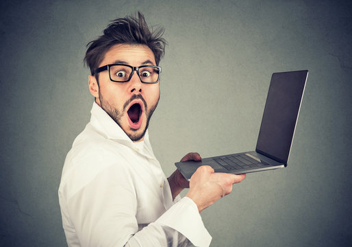 Astonished young man holding laptop