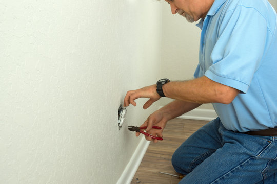 Professional electrician or experienced home owner man using tools to disassemble an electrical outlet for fixing repairing or replacing a broken electric socket