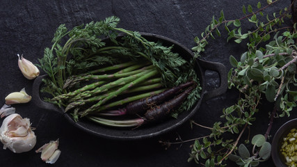 Asparagus and Purple Carrots with herbs for roasting in a Cast Iron Skillet.