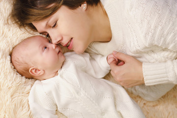 Mother and newborn daughter lie on pink plaid. They are dressed in warm knitted white sweaters. Maternal love and care. Face to face