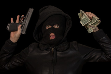 masked criminal surrenders with the gun and the money in hand