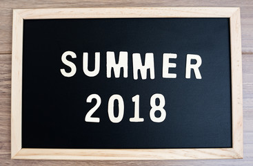 summer word wood text  and 2018 happy new year on Blackboard and black background