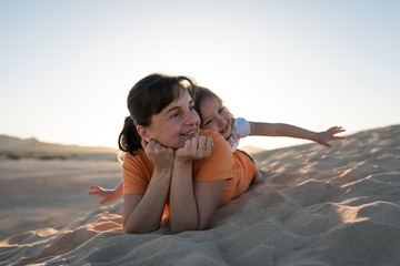 Smilling mother with her cute daughter lie in the sand