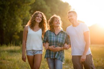 Outdoor portrait of smiling happy senior mother with her children