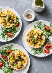 Vegetarian savory hands pie with porcini mushrooms, leeks, potatoes and arugula, tomatoes salad on grey background, top view. Mediterranean style lunch, snack, appetizer, breakfast