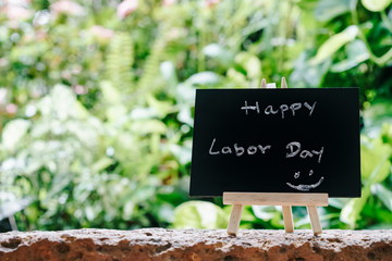 Happy labor day greeting card concept, Chalk board with text HAPPY LABOR DAY with green fresh garden background
