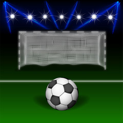 Soccer ball on against an empty soccer goal, in a stadium with lighting.