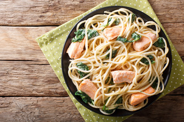 Creamy spaghetti with salmon and spinach close-up on a plate. Horizontal top view