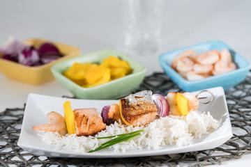 Fischspieß angerichtet auf einem Teller mit Reis mit den Zutaten in Schälchen