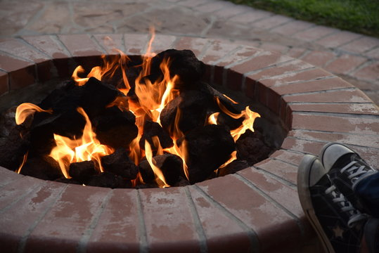 Backyard brick fire pit with someone resting their shoes on the edge