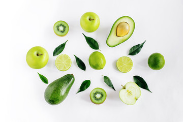 Green  fruits avacado, apples, lime and leaves creative concept top view on the white background.