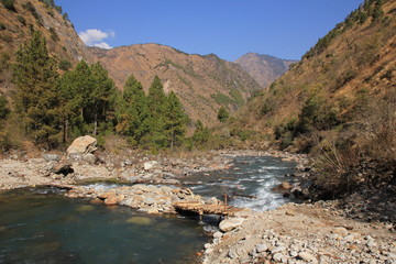 Simple timber bridge and Langtang Khola, river in Nepal. Scene near Shyaphru Besi. Langtang National Park.