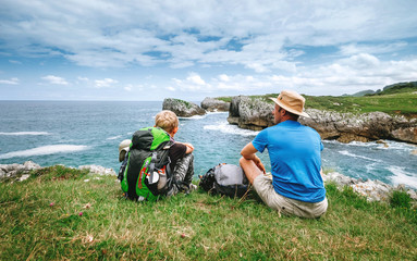 Father and son backpackers rest on the rocky sea side