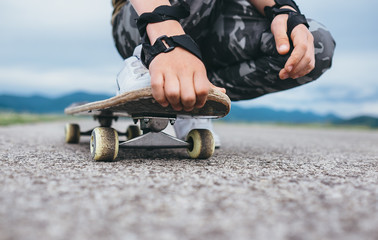 Boy sits on the skateboard legs and hands closeup image