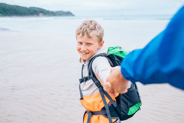Backpacker boy traveler takes his father hand on the ocean coast