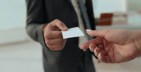 Close-up of two businesspeople exchanging visiting card