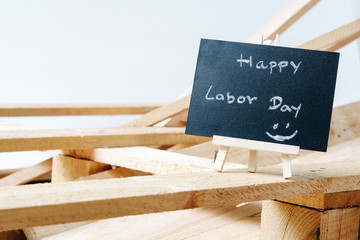Small chalk board with text Happy Labor Day with wooden pallet background on white background. International Workers' Day