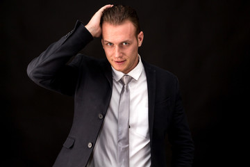 Businessman in black suit standing isolated on black background