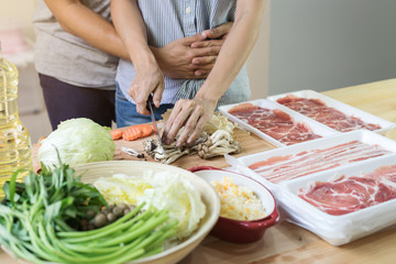 Young asian couple cutting vegetable in the kitchen