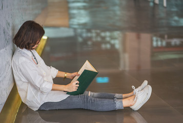 Beautiful young woman with book sitting on floor