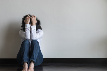 Anxiety disorder menopause woman, stressful depressed emotional felling person with mental health illness, headache and migraine sitting sadly with back against wall on the floor in domestic home