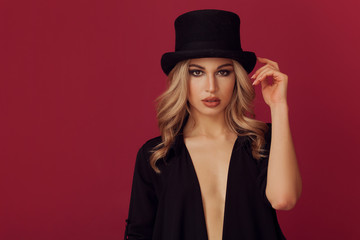 Gorgeous blonde woman portrait wearing top hat and looking at camera