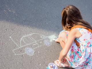 girl paints with chalk on the asphalt