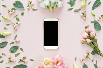 Top view of pink desk with modern gold mobile phone and flower frame