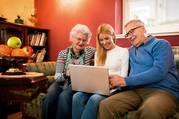Family using a computer sitting on couch and having happy smiling time