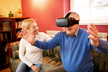 Senior man using virtual reality simulator and having fun with new experience