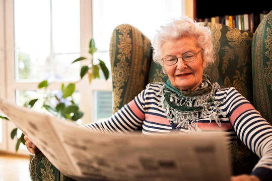 Senior woman in pansion relaxing at home while reading a newspaper