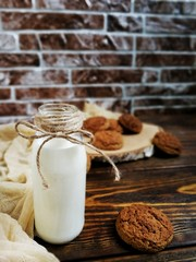 milk in a small bottle with oatmeal cookies and cones on a wooden table and beige runner