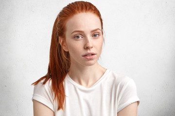 Portrait of serious beautiful ginger woman with freckled skin, dressed in casual white t shirt, has thoughtful expression, poses against concrete wall. Isolated shot of good looking red haired female