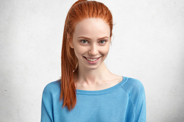 Horizontal portrait of happy young female model with cheerful expression, has red bright pony tail, dressed casually, smiles pleasantly, rejoices recieve compliment from male, isolated over white wall