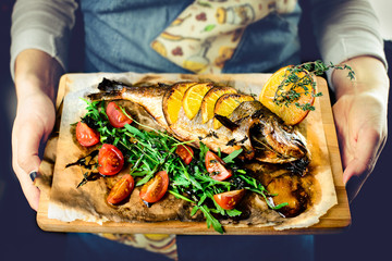 Unidentified chef giving wooden board with delicious fish served with tomatoes, lemon and herbs in a restaurant. Toned image