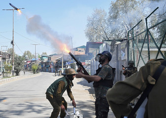 An Indian policeman fires a tear smoke shell towards protesters during funeral of Mussavir Ahmed Wani, a suspected militant, who according to local media reports was killed in a gunbattle with Indian security forces on Friday, in south Kashmir's Pulwama