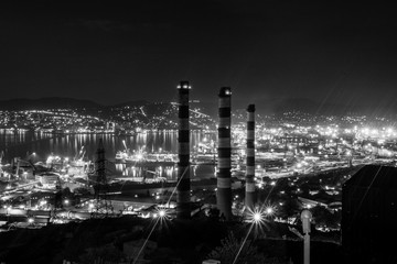 Night view of the Novorossiysk town with the plant's pipes at front , Black Sea coast. Lights glow at night and make feeling of science fiction landscape.