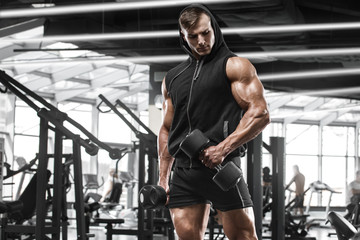 Muscular man working out in gym doing exercises, strong male bodybuilder