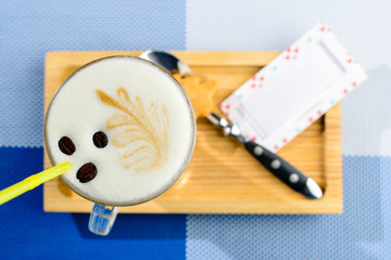 Cappuccino in a glass on the wooden board and card with copyspace for text. Top view, flat lay