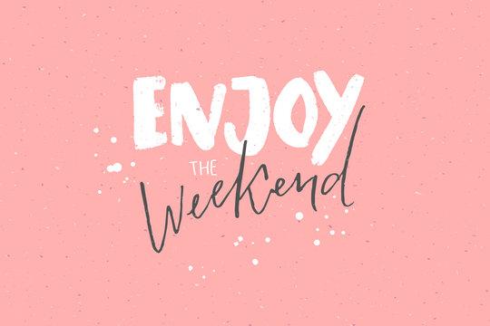 Enjoy the weekend. Inspirational caption, handwritten text on pastel pink background