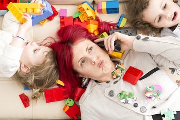 Tired Mom on Phone with Kids Lying on Plastic Bricks