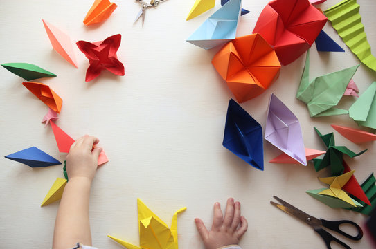 the child makes origami. Multicolored Origami and paper on  a white table. origami lesson