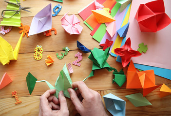 Man doing origami. Multicolored Origami and paper on  a wooden table.lesson of origami