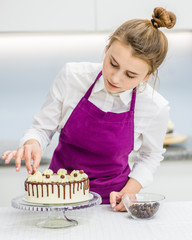 Young woman decorating chocolate cake in the kitchen