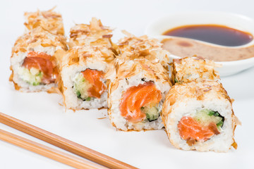 Traditional Japanese cuisine. Tasty sushi rolls with rice, cream cheese, salmon and tuna on light background
