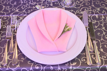 Formal table setting with silverware placed in the order of use, and elegantly wrapped napkin in the shape of a jacket on top of white china, ready for guests at an event, wedding or at a restaurant