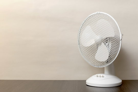 white desk oscillating fan, toned, copy space