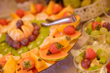 Colorful fruit platter with a large variety of exotic and season fruit, prepared for a food bar, reception or any type of celebration, in tune with any vegan choices, and today's healthy living mantra